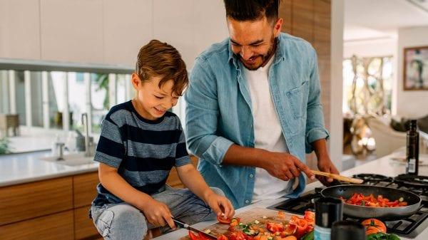 Papa e hijo cocinan juntos.